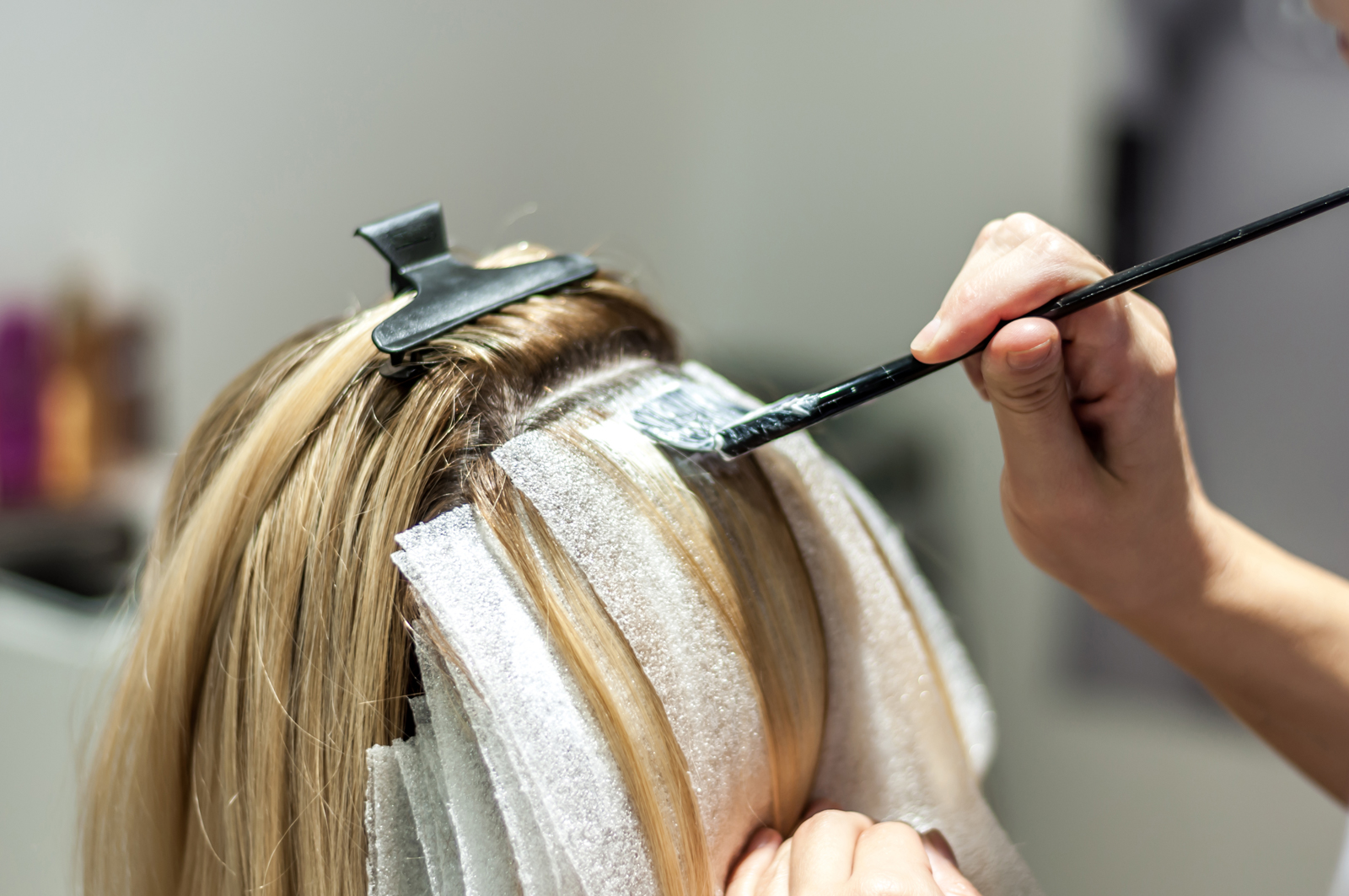 A woman having her roots done at the hairdressers.