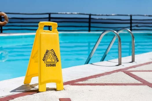 Wet floor sign by hotel swimming pool