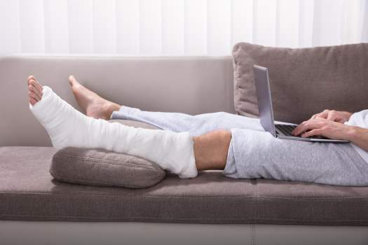 person lying on a sofa with their leg in a plaster cast