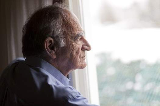 Older man looking out of the window