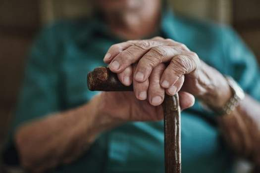 Close up of old man's hands with cane