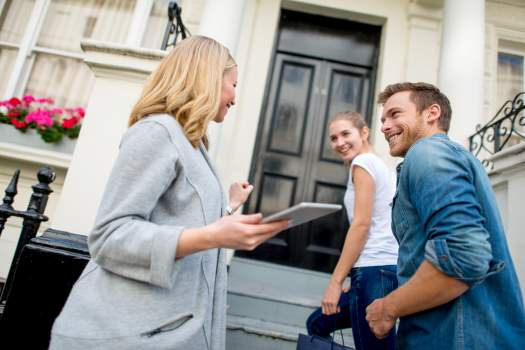 Estate agent giving young couple keys to their new home